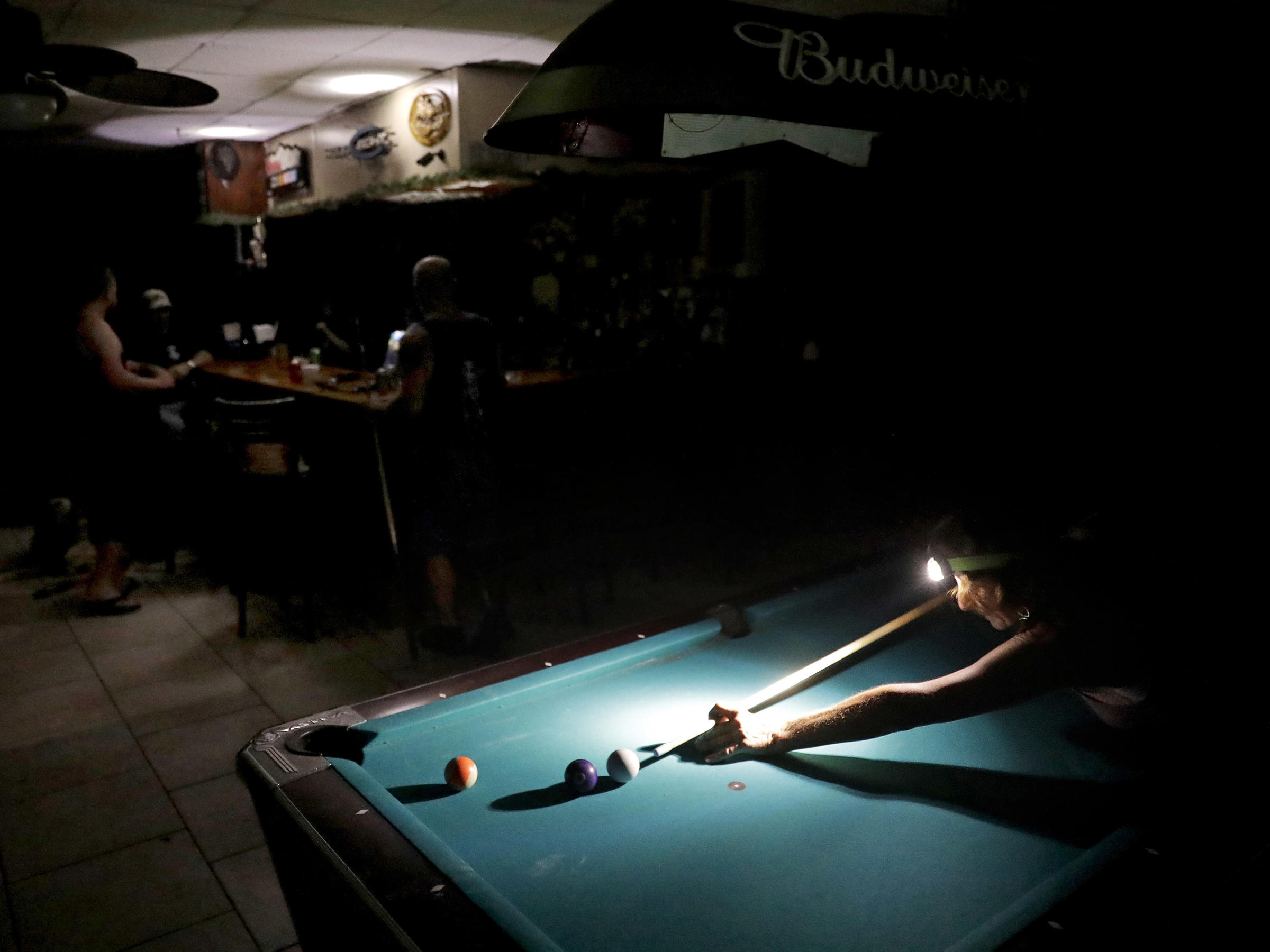Playing pool during a power outage from Hurricane Irma Lisa Borruso used a headlamp to line up a shot at Gators&#039 Crossroads in Naples Fla. Monday. Millions of people had their power knocked out by the storm — and some outages will continue for