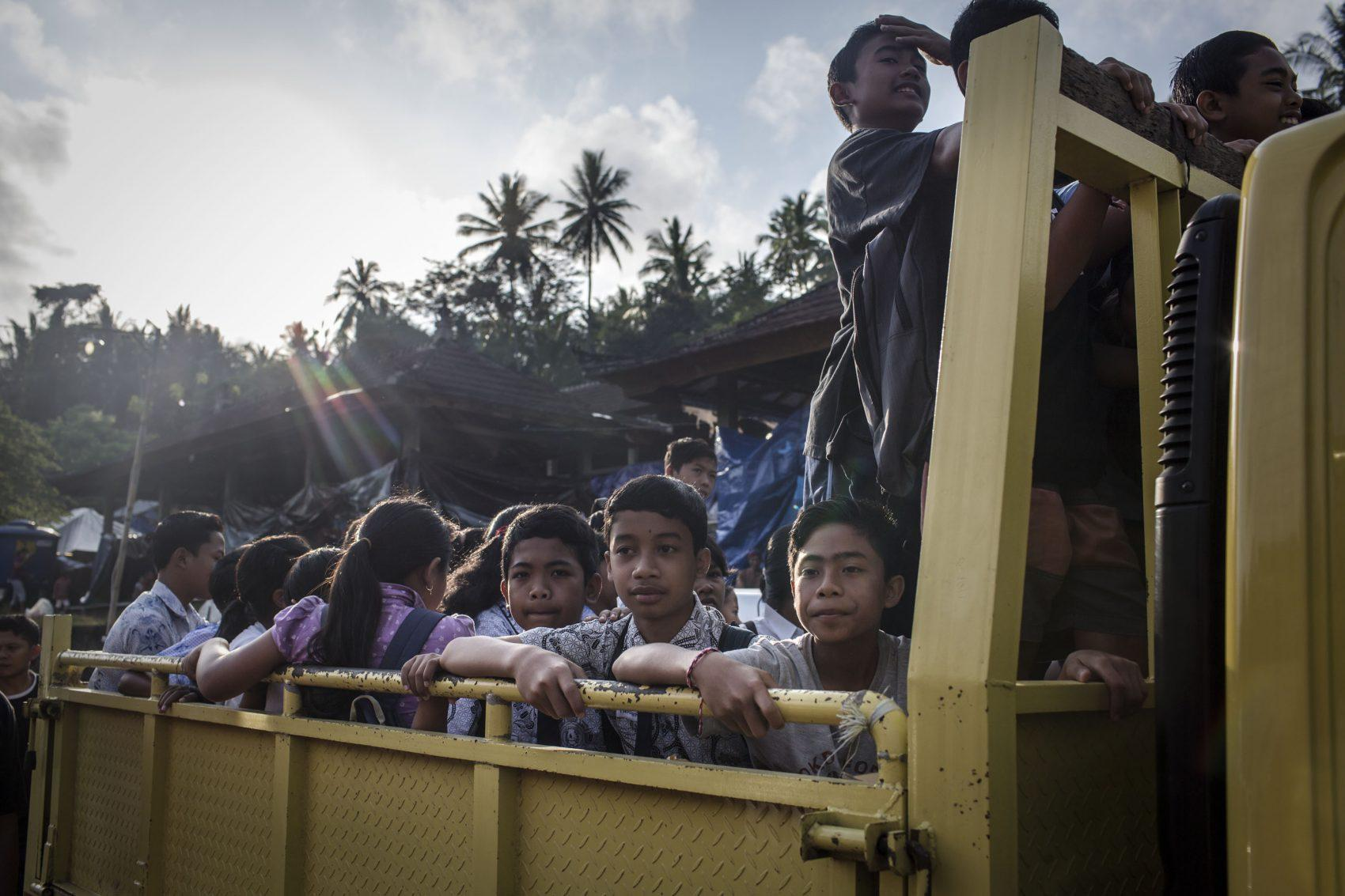 Evacuee children on a truck as they head off to a temporary school on Sept. 27 2017 in Karangasem regency Bali Indonesia. Indonesian authorities declared a state of emergency as hundreds of tremors are recorded at Bali's Mount Agung volcano and
