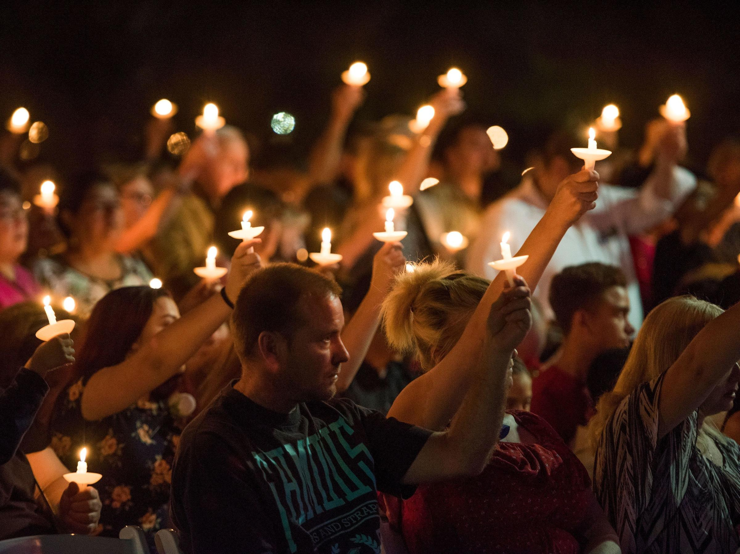People hold up candles at a memorial service for Charleston Hartfield, a Las Vegas police officer who was killed when a gunman opened fire on a country music festival, in Las Vegas, Nevada on Oct. 1.