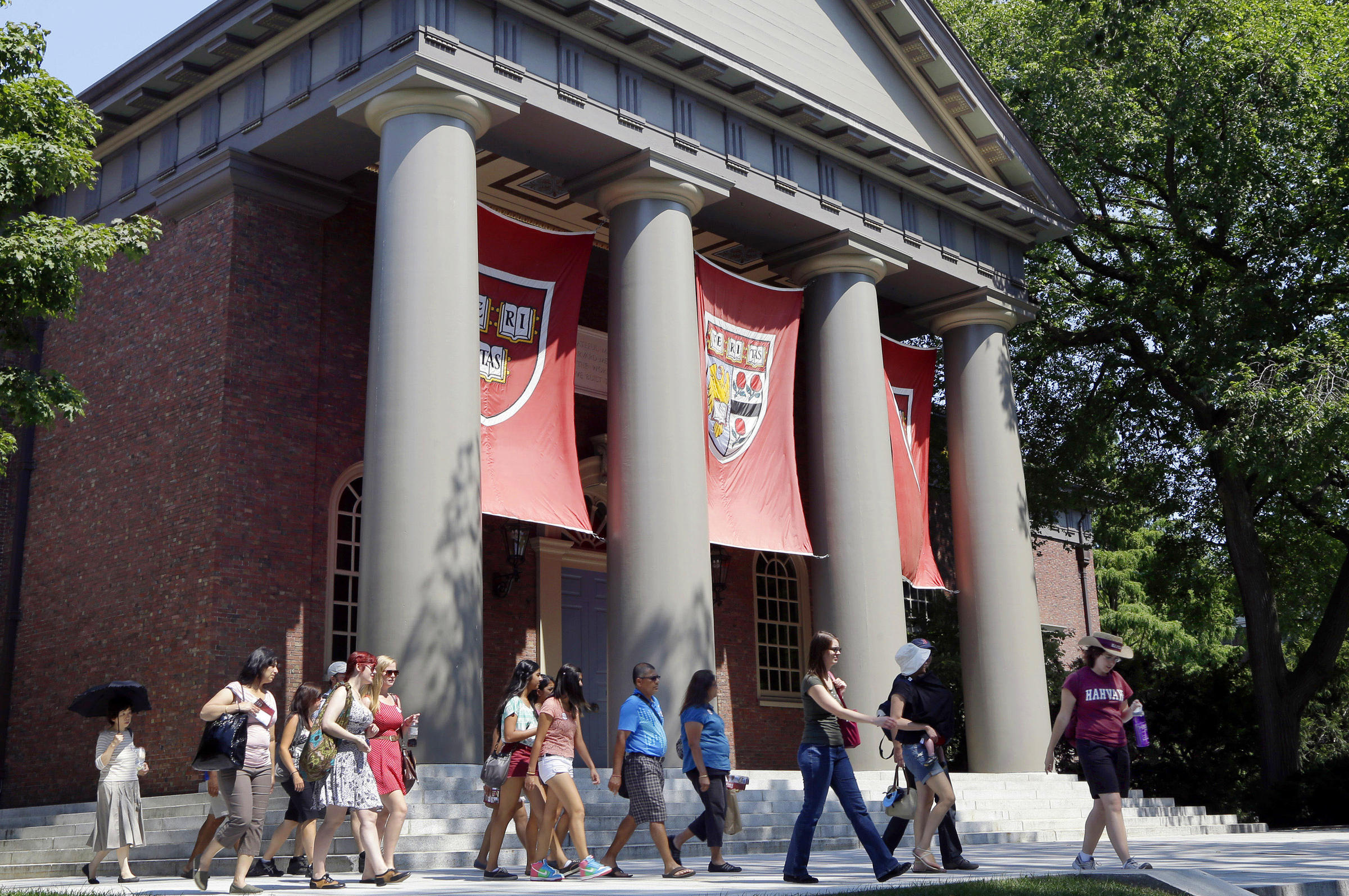 A tour group in 2012 walks through the campus of Harvard University in Cambridge Mass