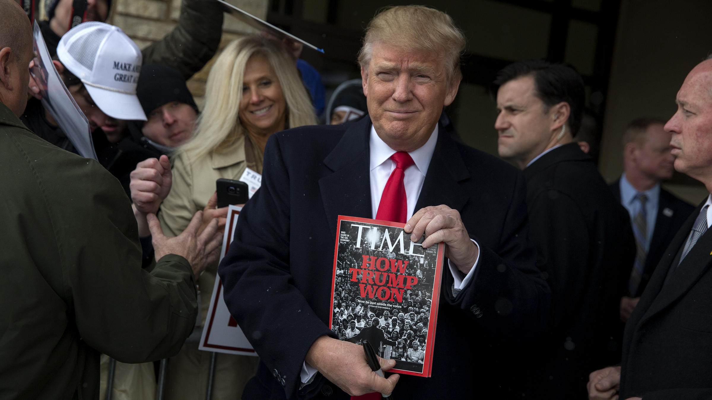 Donald Trump holds a copy of Time magazine in January 2016 in Winterset Iowa. His golf clubs have displayed fake Time covers featuring Trump
