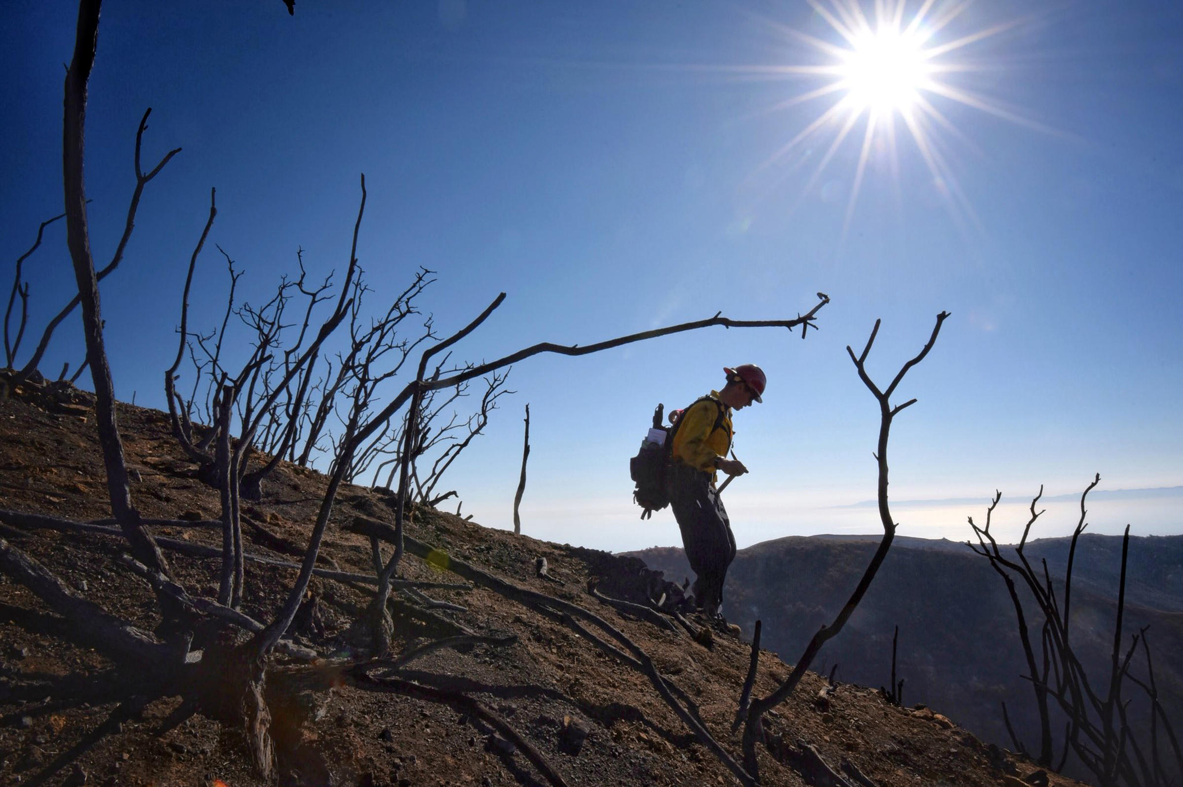 Santa Barbara County Fire Capt. Ryan Thomas hikes down steep terrain rendered barren by the Thomas Fire last month. Authorities announced Friday they had reached 100 percent containment of the fire which is the largest in modern California history