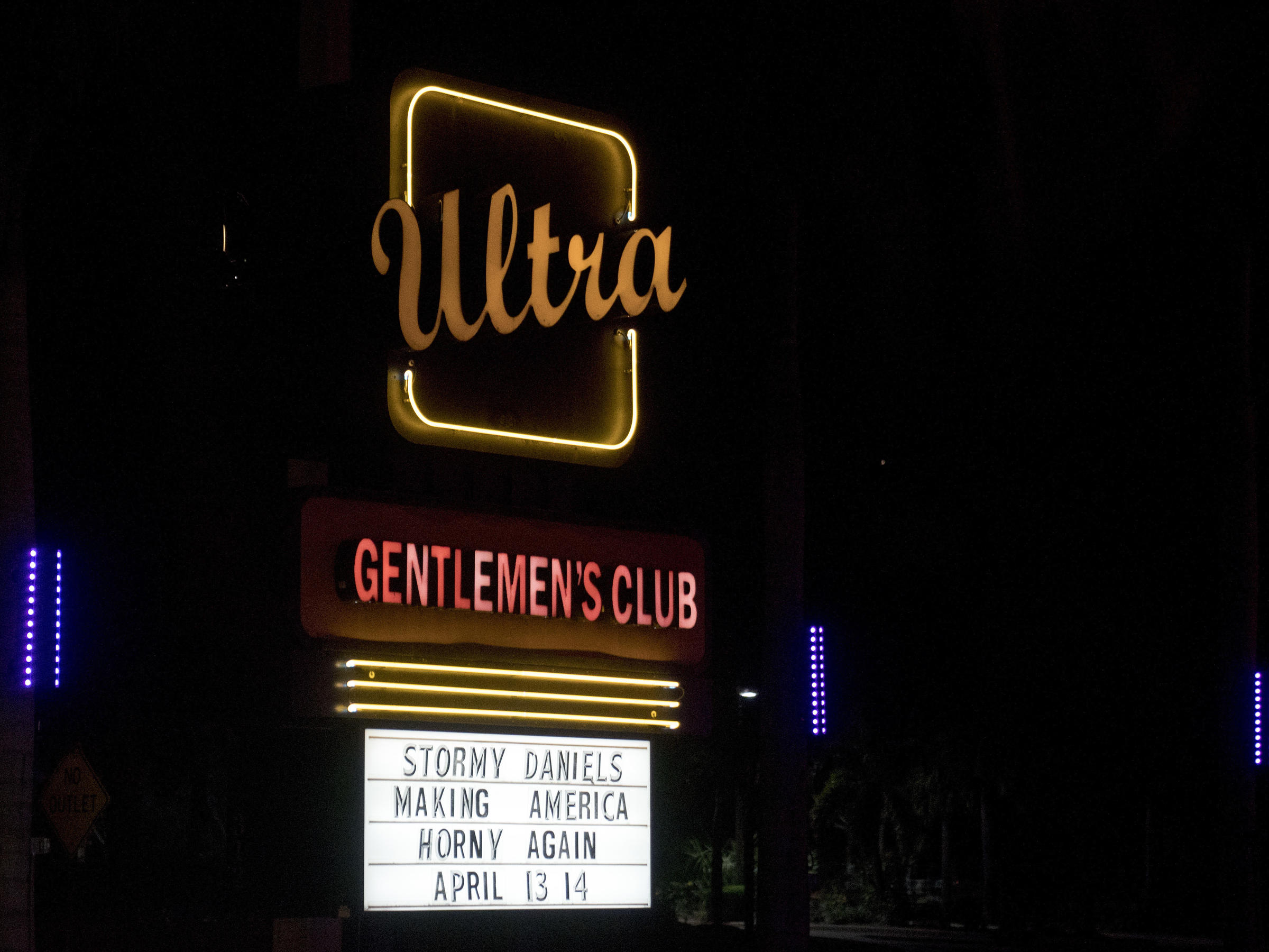 A sign for a Gentlemen's Club across the street from Trump International Golf Club reads