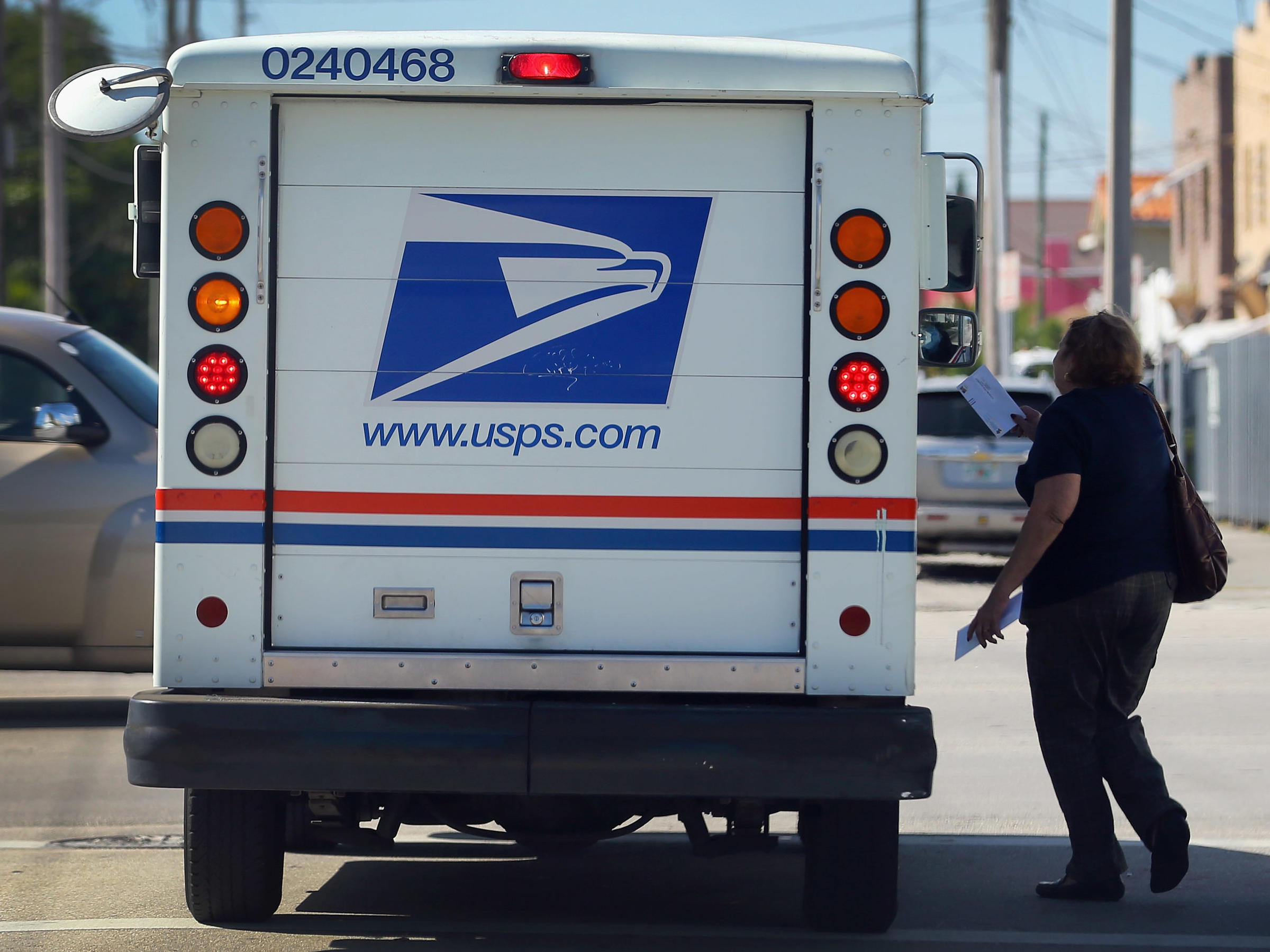 a women tries to give a letter to the driver of a us postal service truck on nov 15 2012 in miami