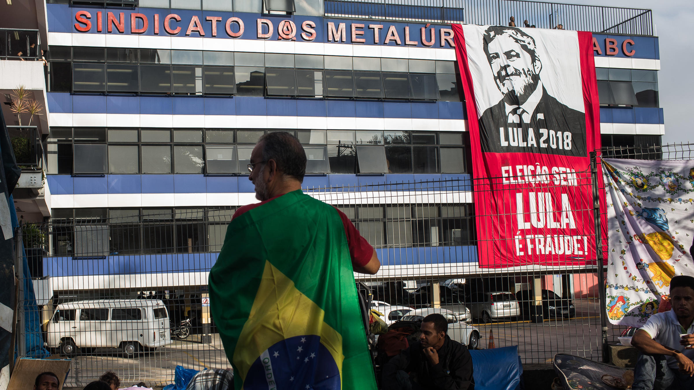 A supporter of former President Luiz Inacio Lula da Silva waits in front of the building where Lula holed up after defying a court order to turn himself