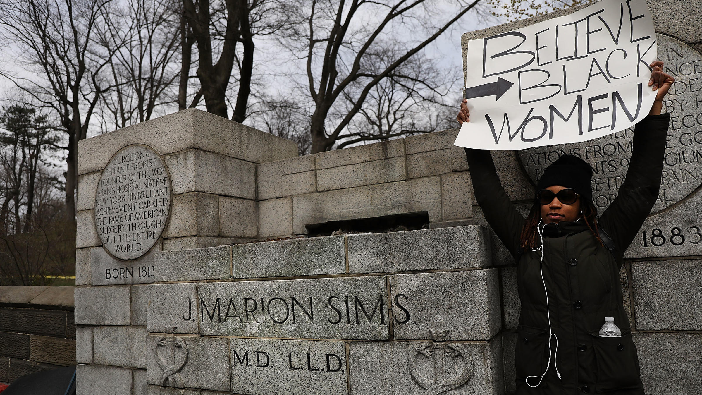 A woman stands beside the empty pedestal where a statue of J. Marion Sims used to stand. Multiple groups demanded the removal of the statue which sat on a pedestal praising his achievements as