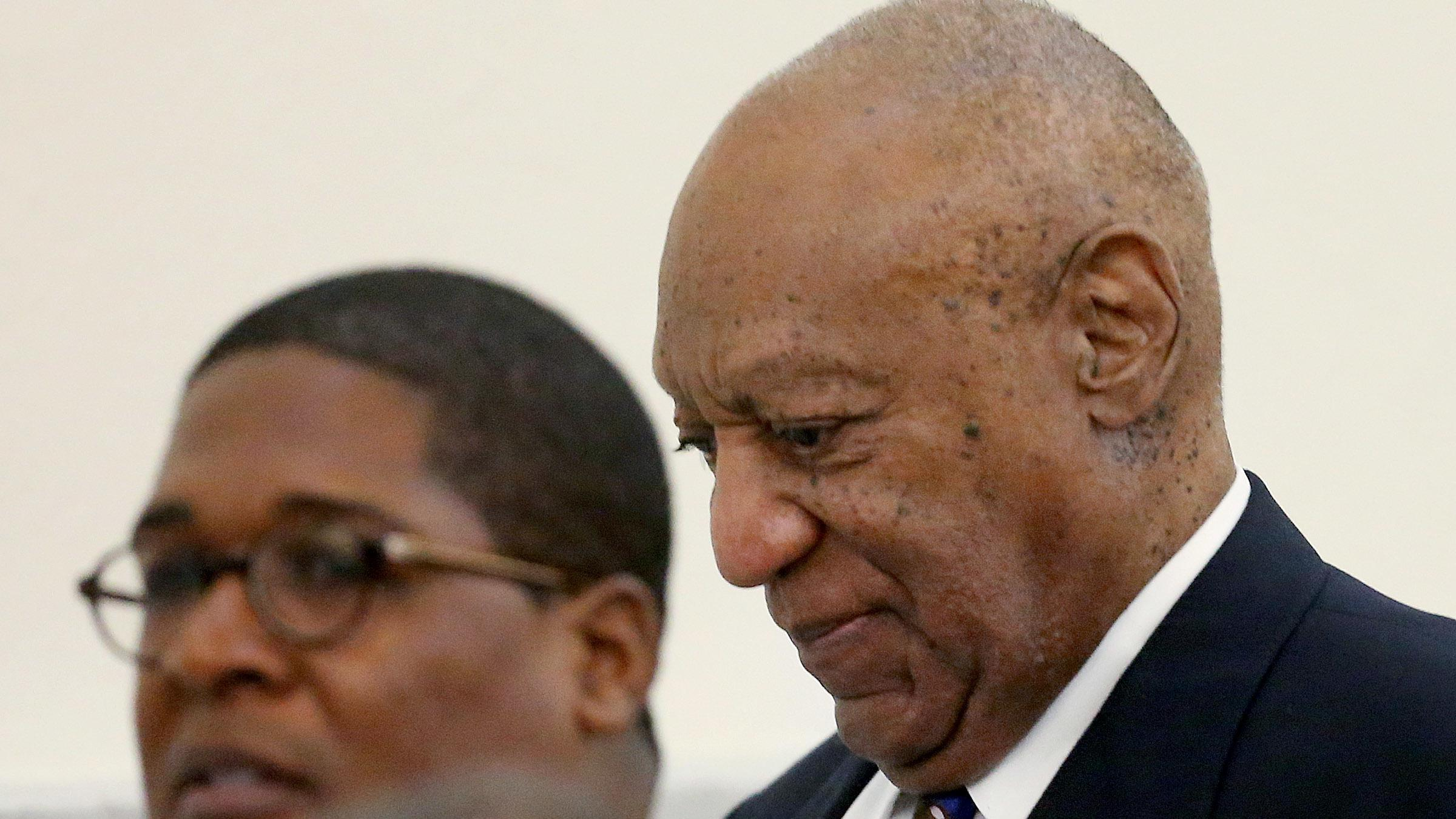 Bill Cosby, right, walks through the Montgomery County Courthouse with his  spokesman, Andrew Wyatt during a break in his sexual assault retrial on  Tuesday.