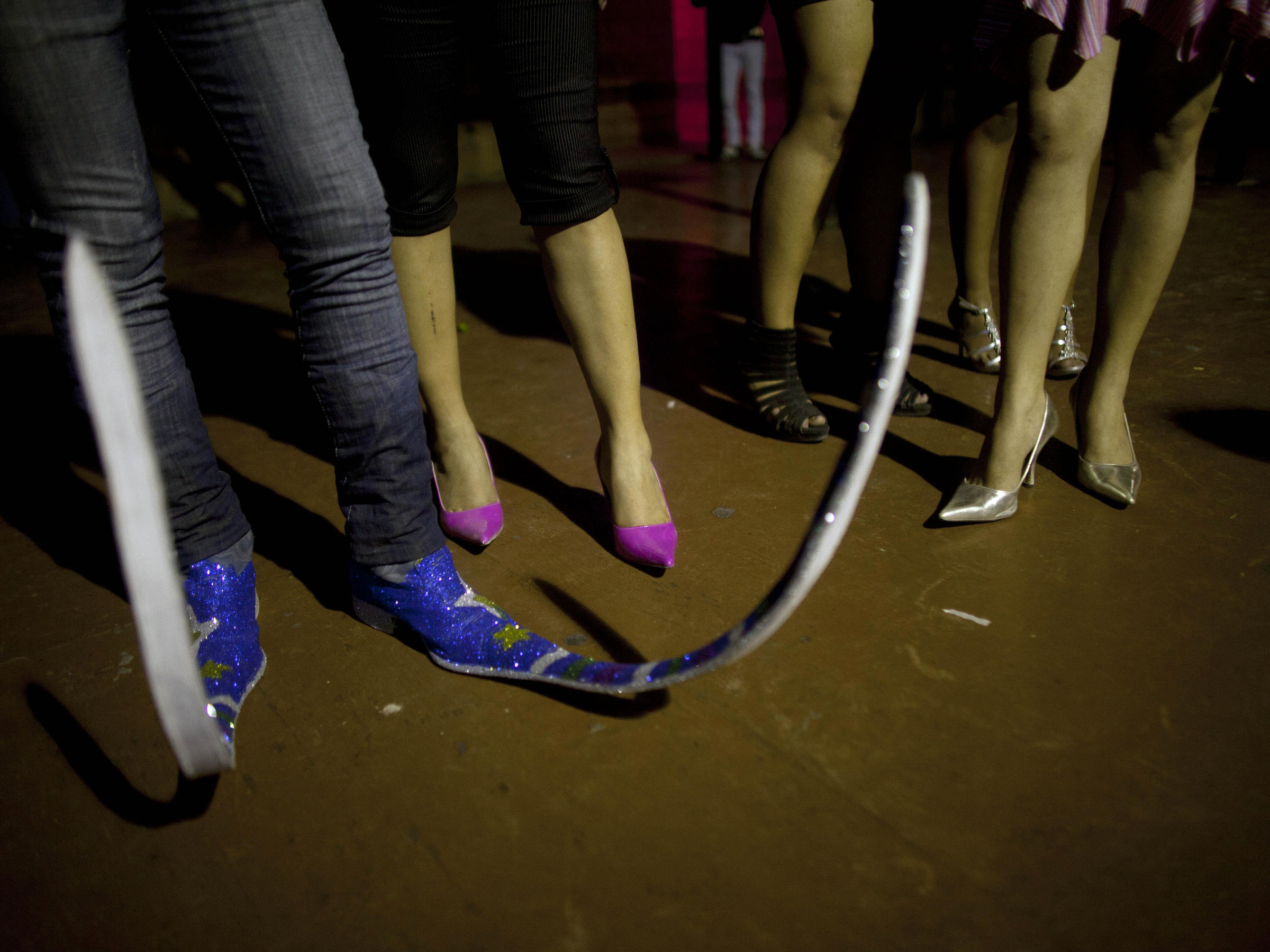 96a616c0f0 A man wearing his extra long pointy boots stands next to women at a  nightclub in Matehuala