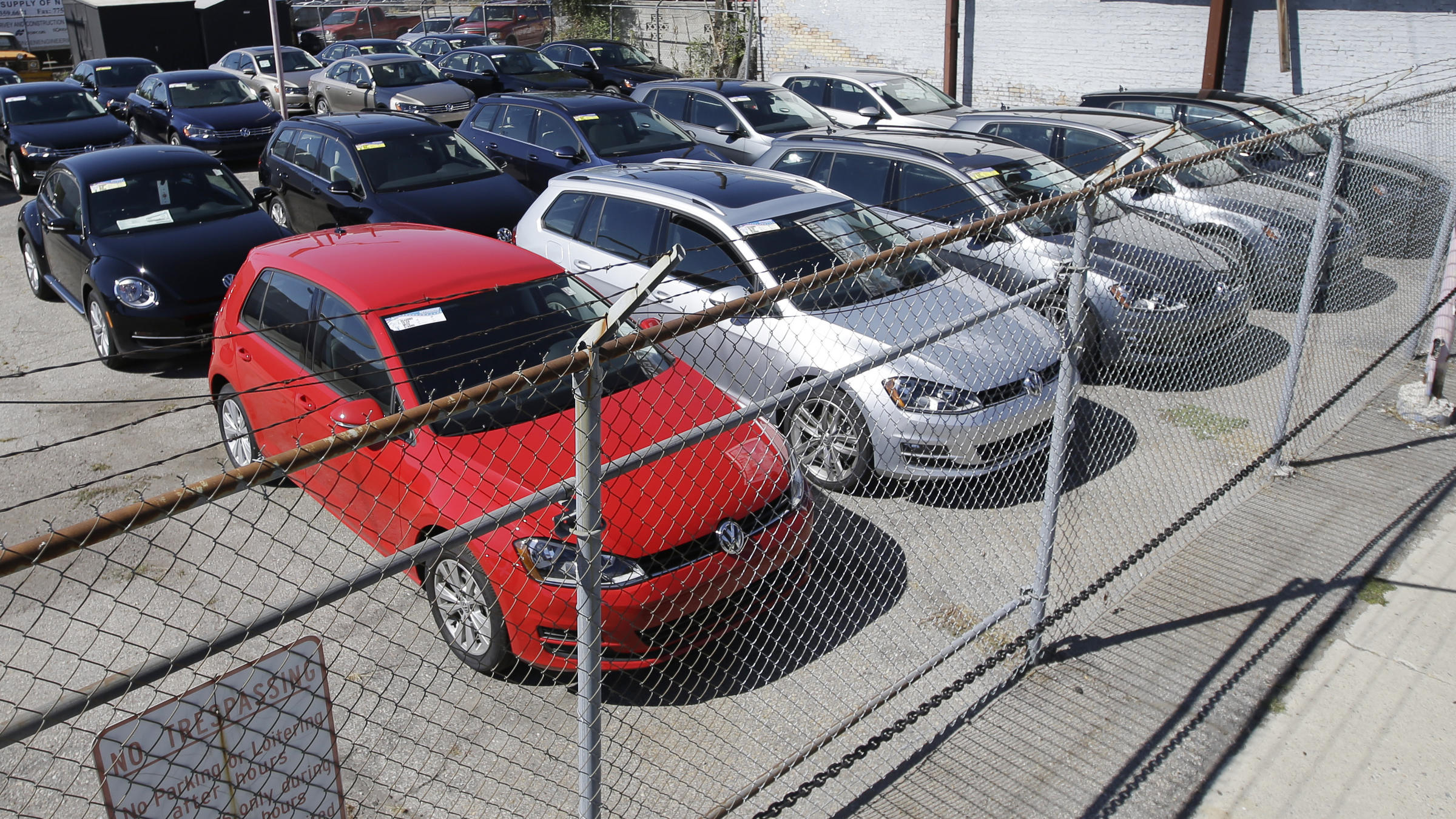 Volkswagen Diesels Are Shown Behind A Security Fence On A Storage Lot Near A  VW Dealership