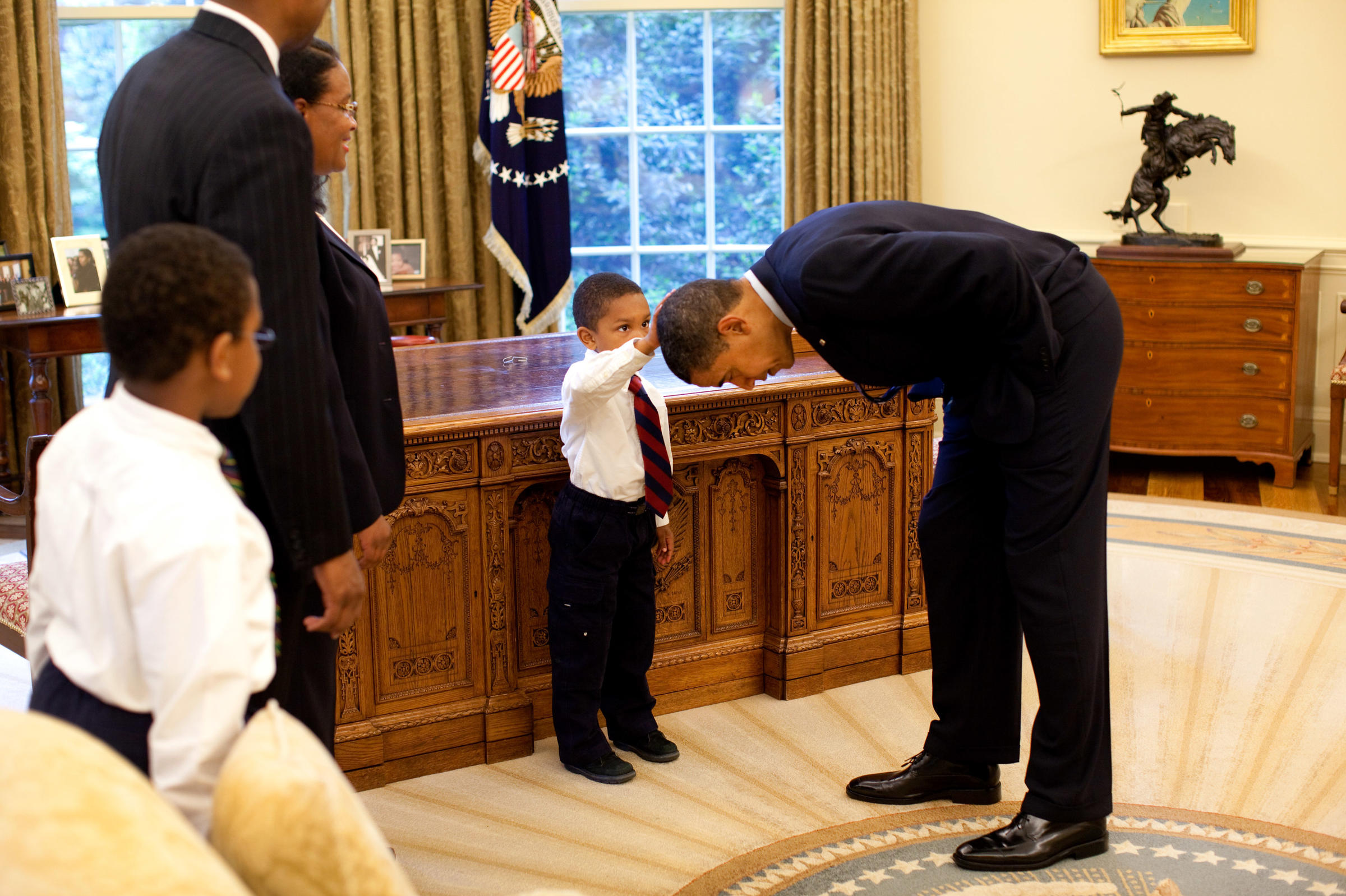 President Barack Bends Over So The Son Of A White House Staff Member Can Pat His Head During Visit To Oval Office On May 8 2009