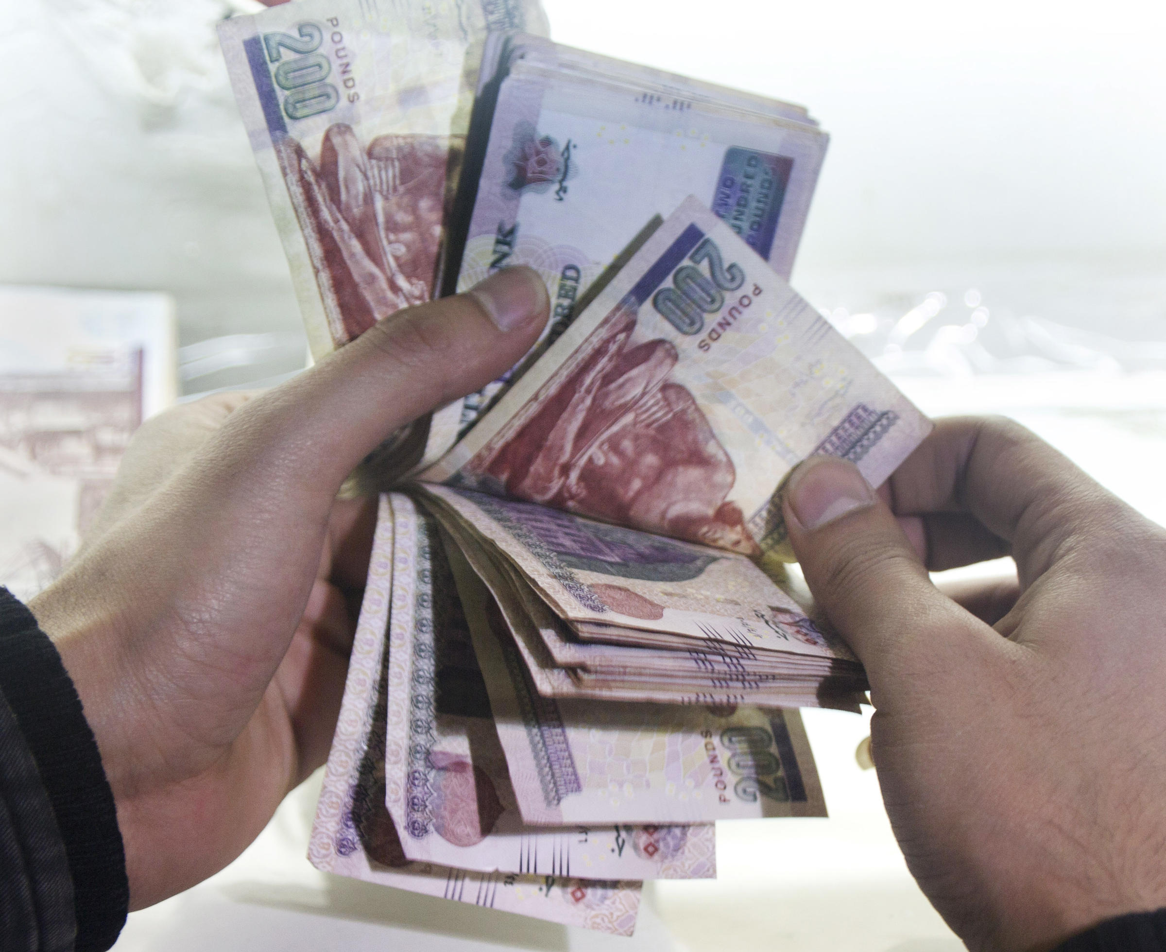 A Man Counts Egyptian Currency At An Exchange Office In Cairo