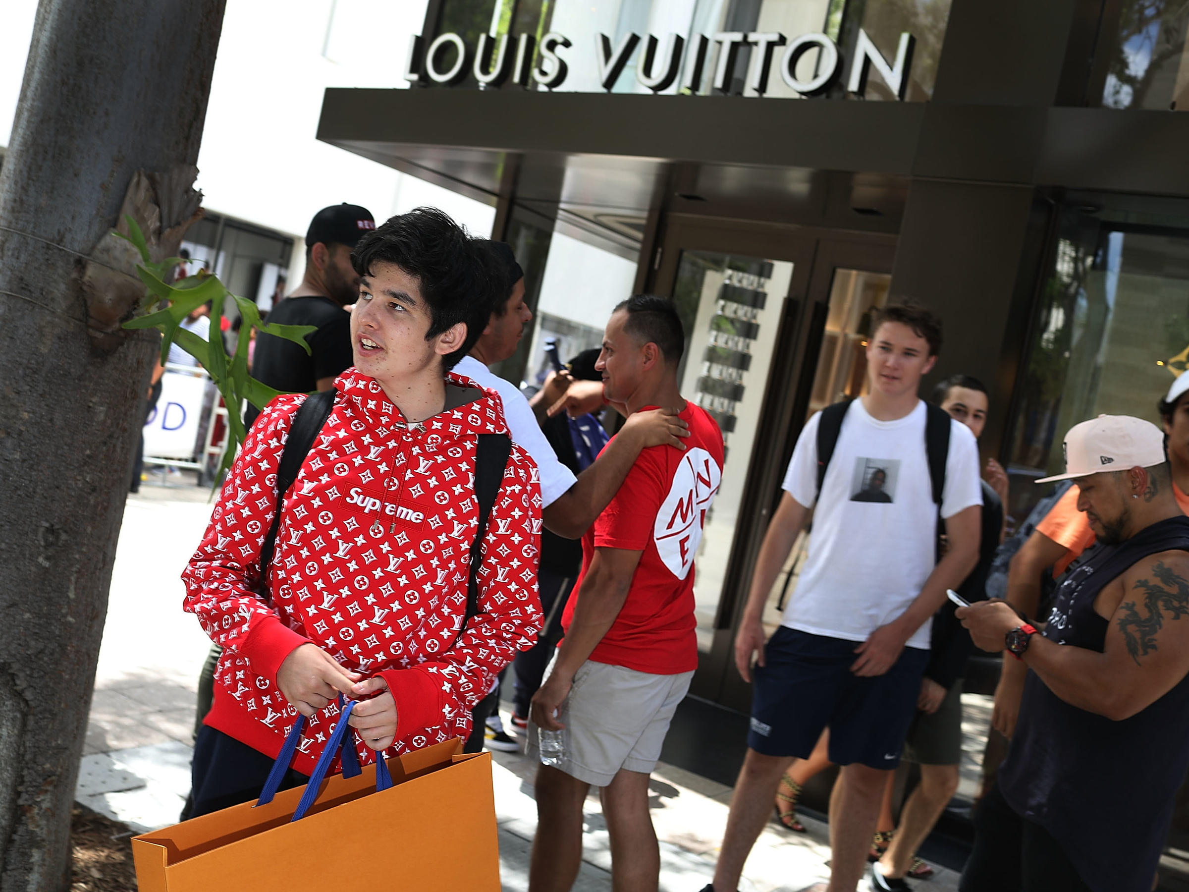 b70fb450d825 Mateo Lorente (left) wears his new Supreme shirt as people flock to a Louis  Vuitton store in Miami to purchase limited-edition Supreme and Louis Vuitton  ...
