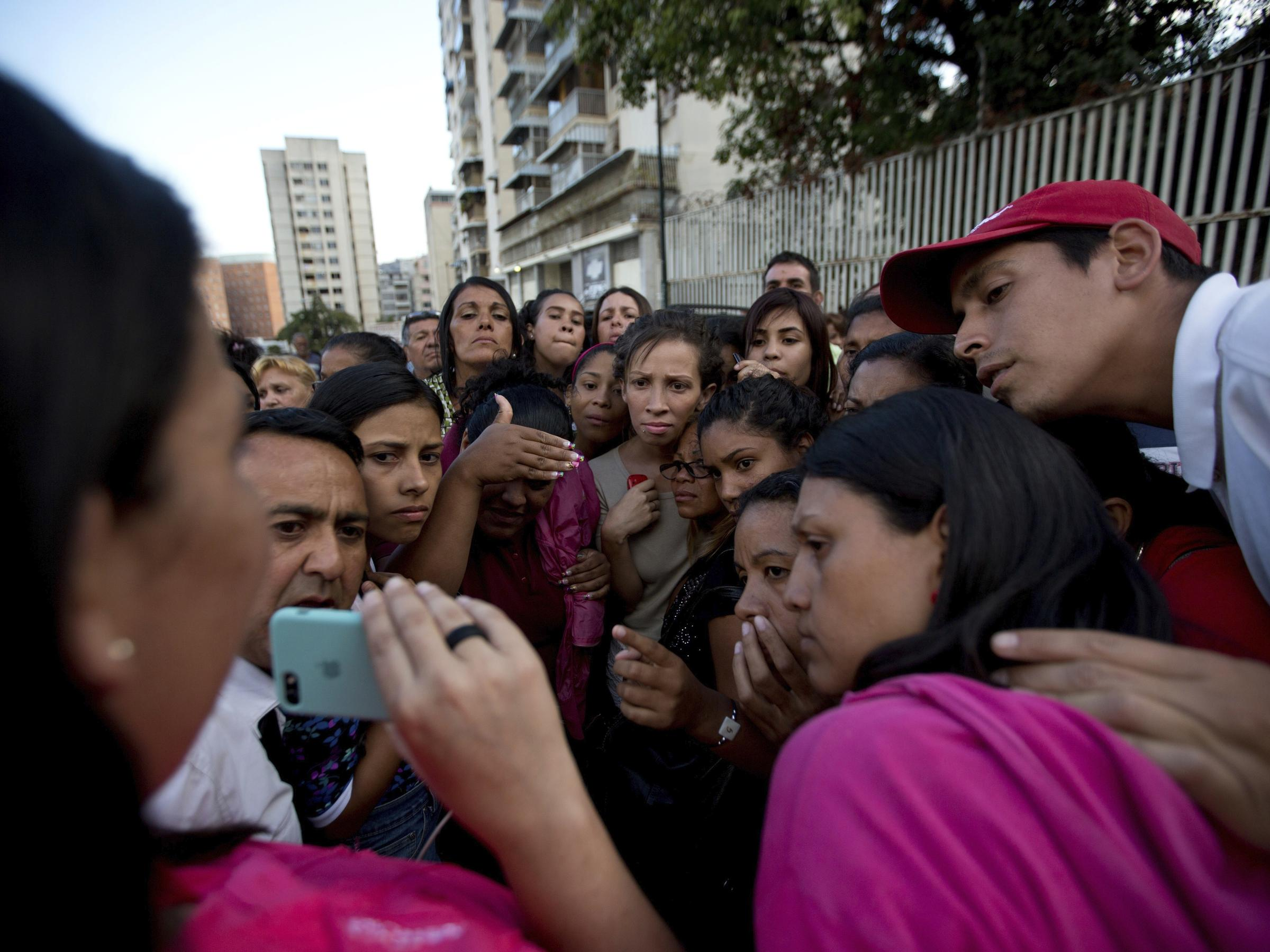 Relatives of prisoners watch in a mobile phone a video released by the prisoners outside of Venezuelan political police headquarters SEBIN in Caracas Venezuela on Wednesday