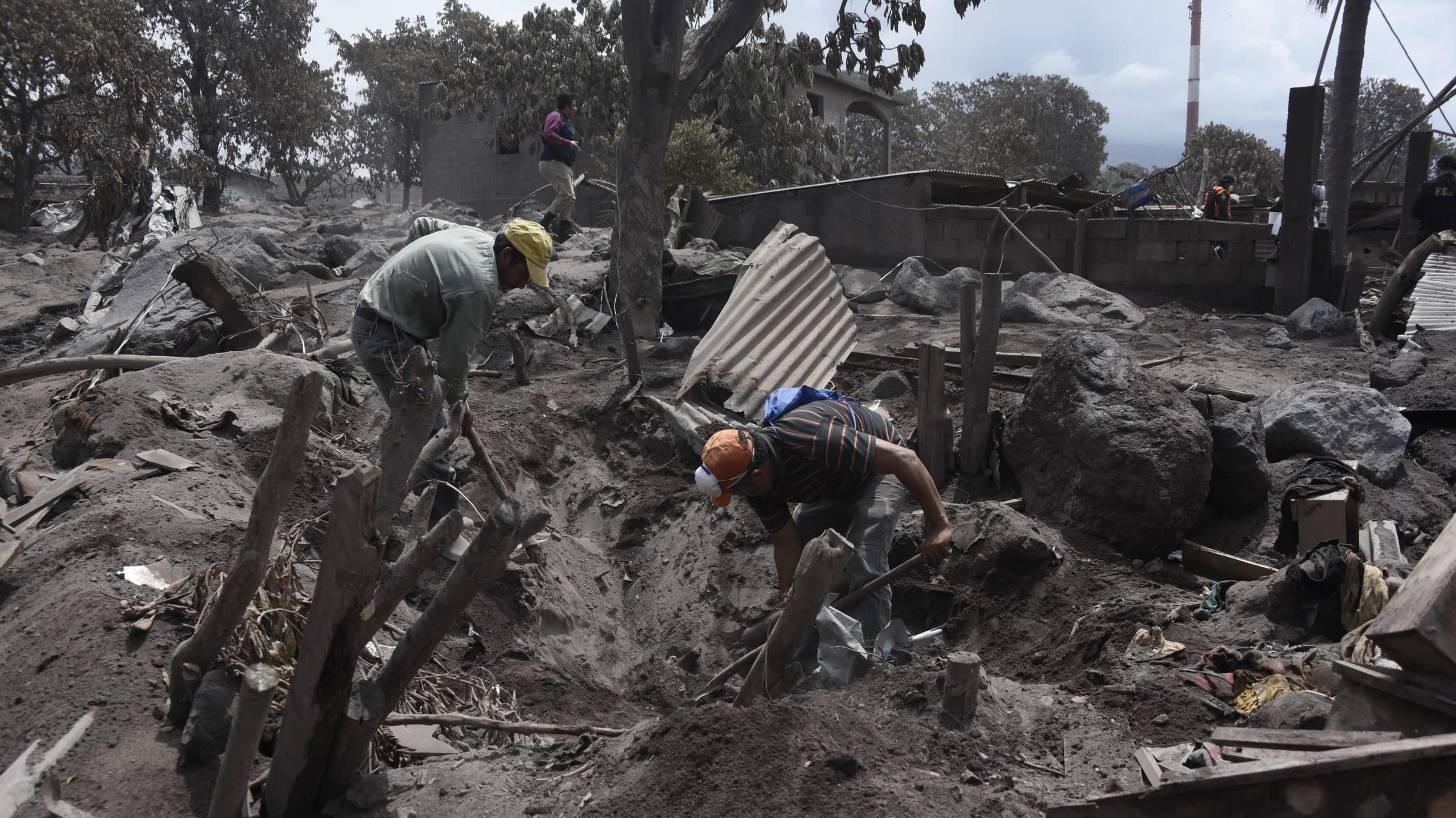 Residents search for victims of the Fuego volcano eruption in the ash-covered village of San Miguel Los Lotes in Escuintla about 20 miles southwest of Guatemala City on Thursday