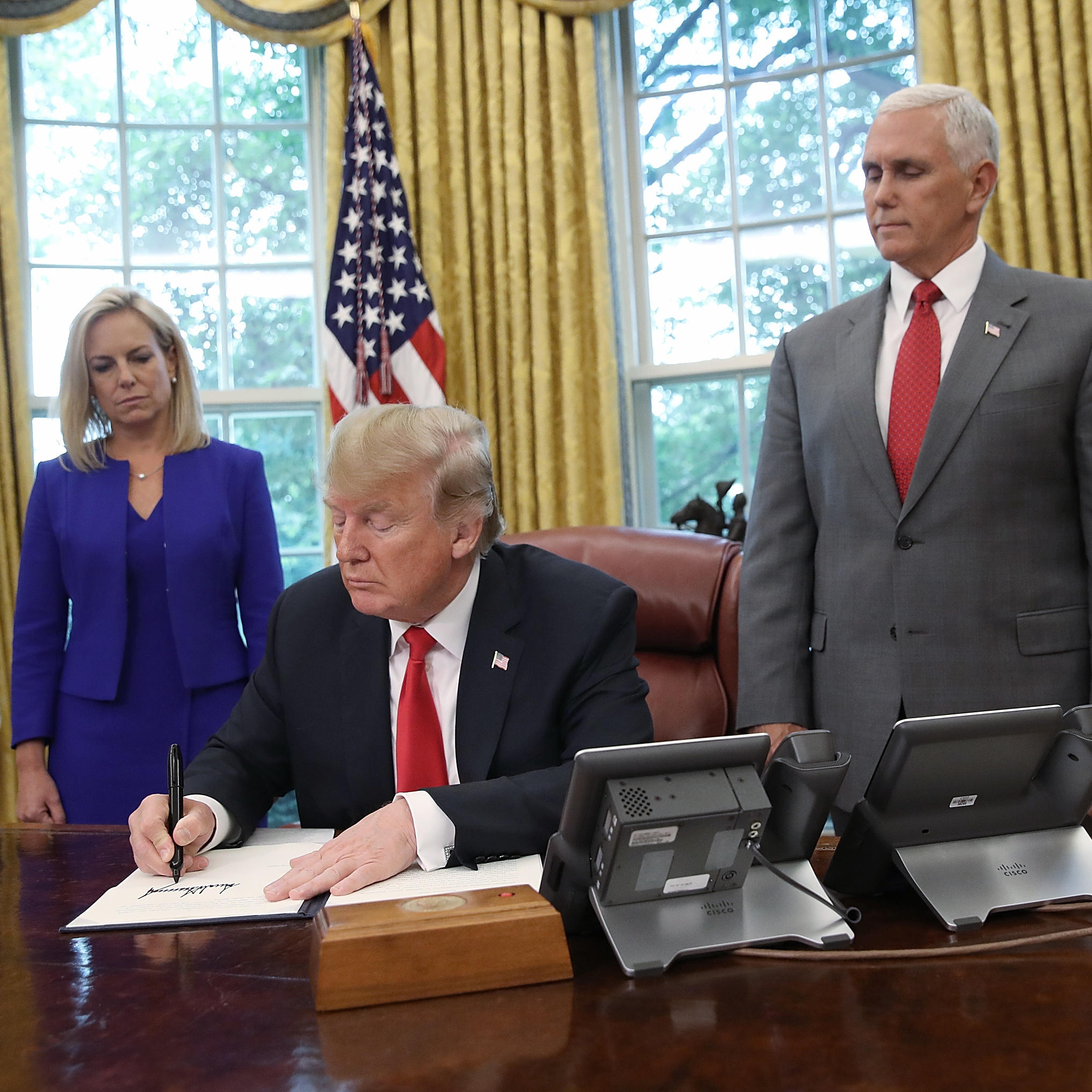 President Trump accompanied by Department of Homeland Security Secretary Kirstjen Nielsen and Vice President Pence signs an executive order regarding detaining migrant families on Wednesday at the White House
