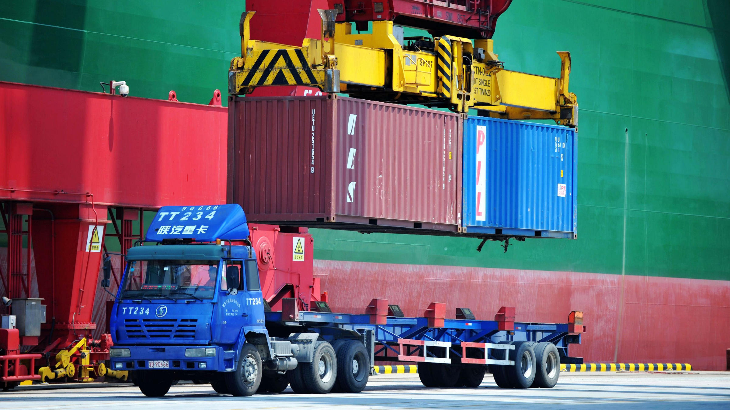 Containers are transferred at a port in Qingdao in China's eastern Shandong province on July 6. China has announced a plan to impose more tariffs on U.S. goods in response to escalating trade threats from the Trump administration