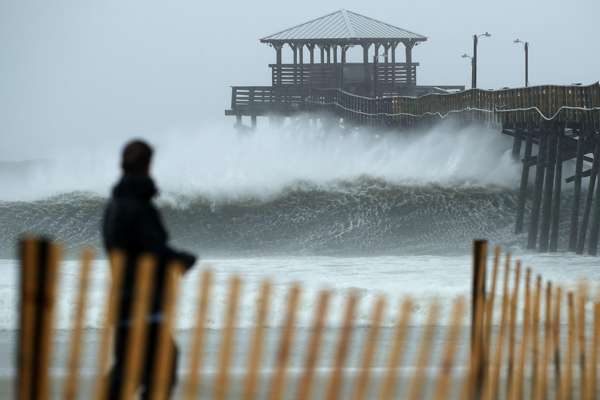 Waves crash underneath the Oceana Pier as the outer bands of Hurricane Florence begin to affect the coast on Thursday in Atlantic Beach N.C. Coastal cities in North Carolina South Carolina and Virginia are under evacuation orders as the Category 2 hurri
