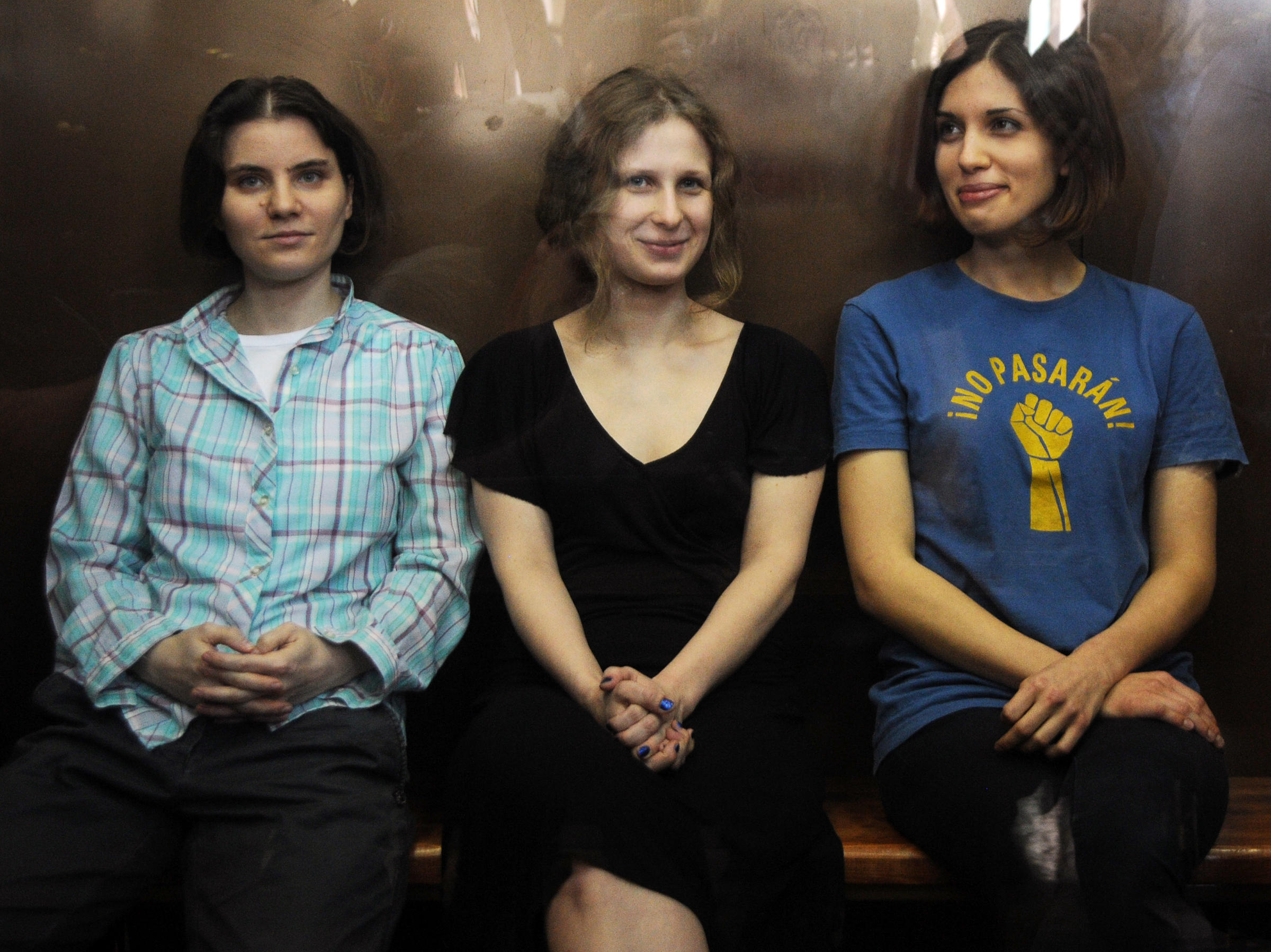 Members of the all-girl punk band Pussy Riot: Nadezhda Tolokonnikova  (right), Maria Alyokhina (center) and Yekaterina Samutsevich (left) in a  glass-walled ...