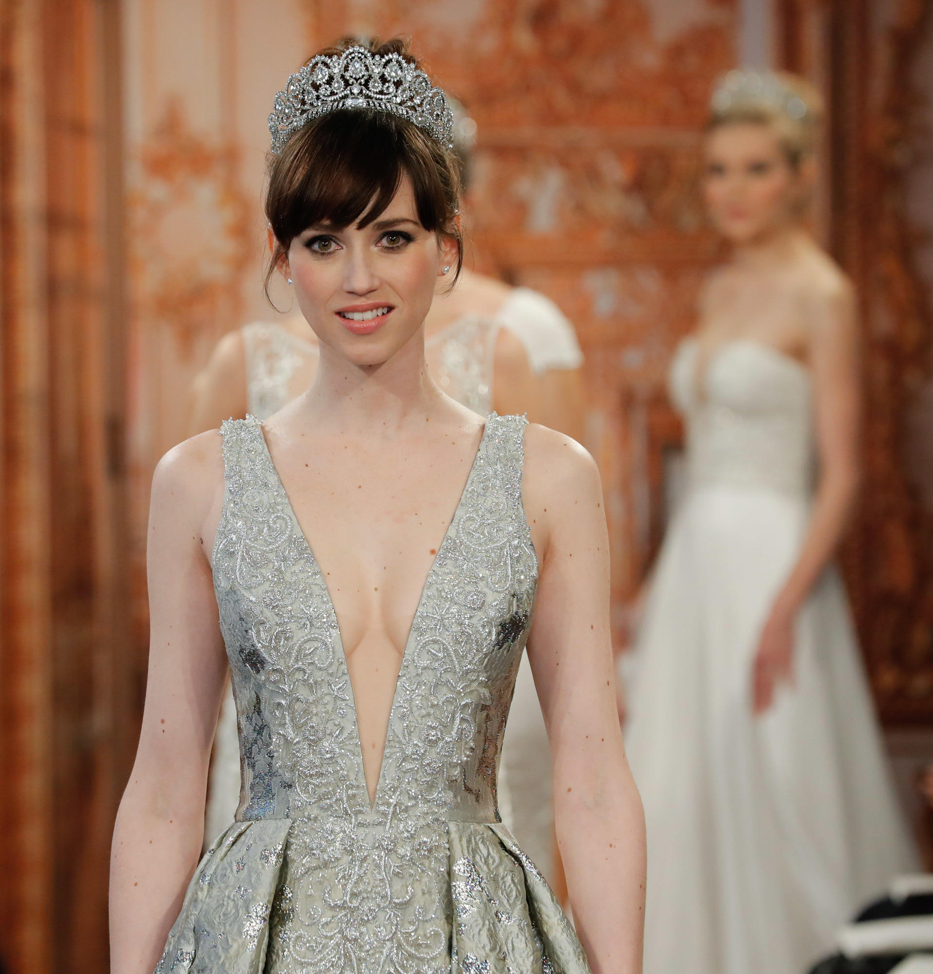 a model walks the runway in a low cut gown at this years bridal fashion week in new york