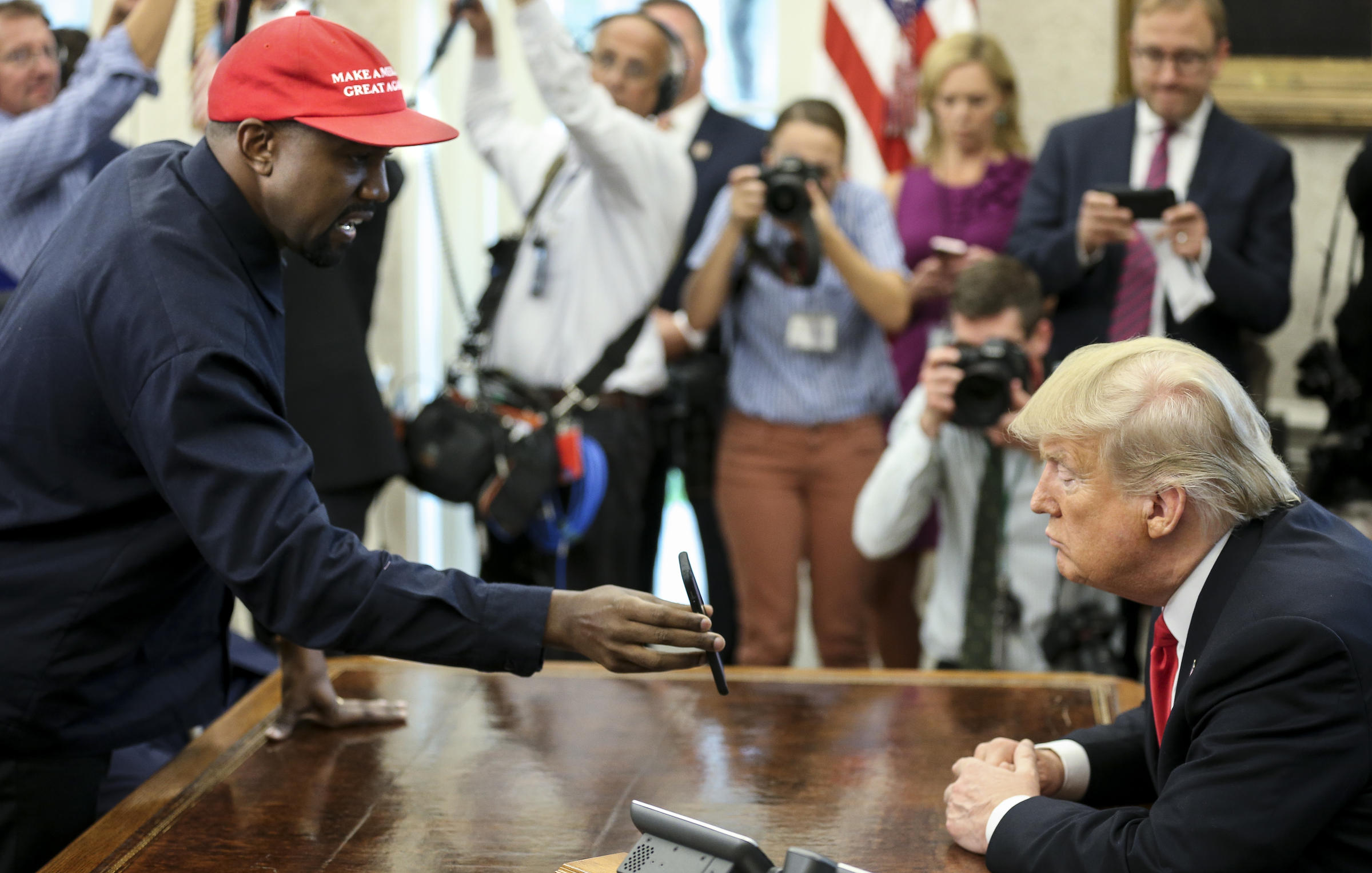 a726503a9e246 Rapper Kanye West shows a picture of a plane on a phone to President Trump  during a meeting in the Oval Office on Thursday.