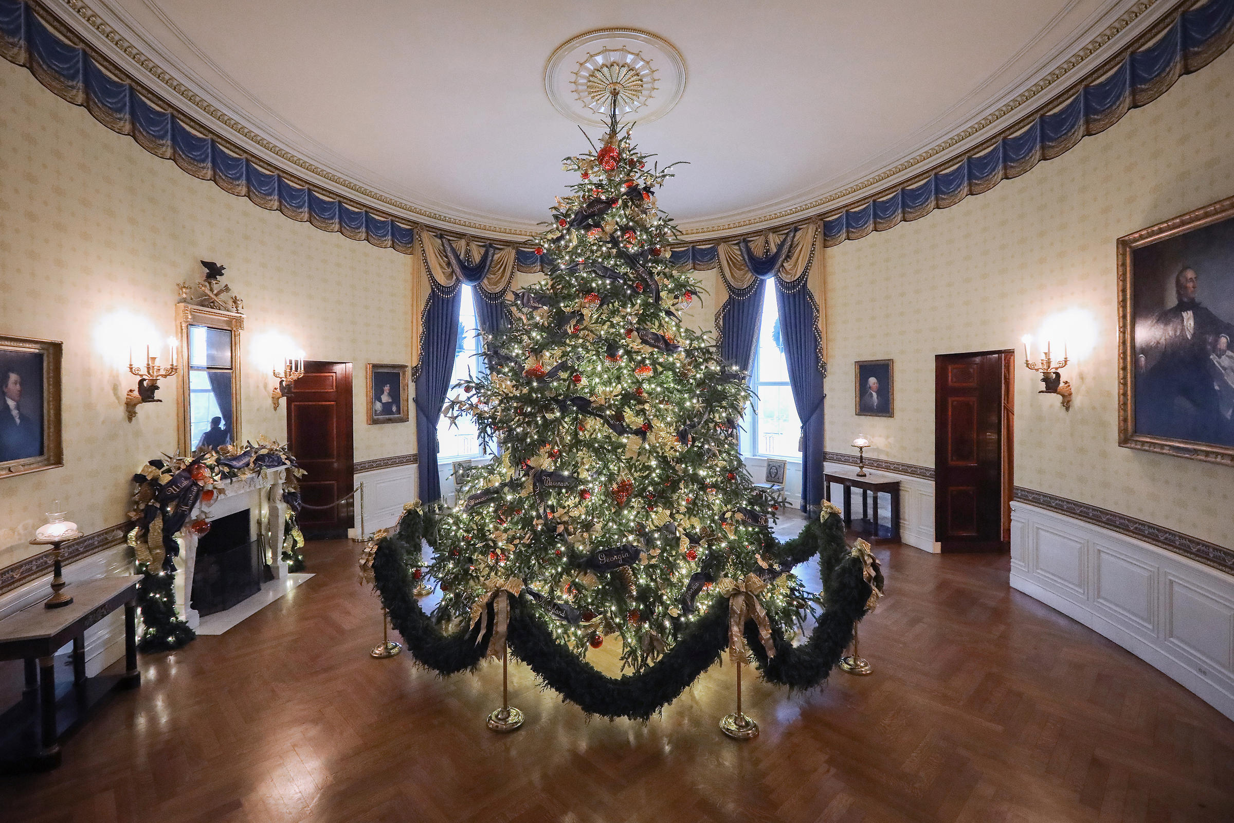 At 18 feet tall the official White House Christmas tree is dressed in over 500 feet of blue velvet ribbon embroidered in gold with the name of each state and territory and is on display in the Blue Room