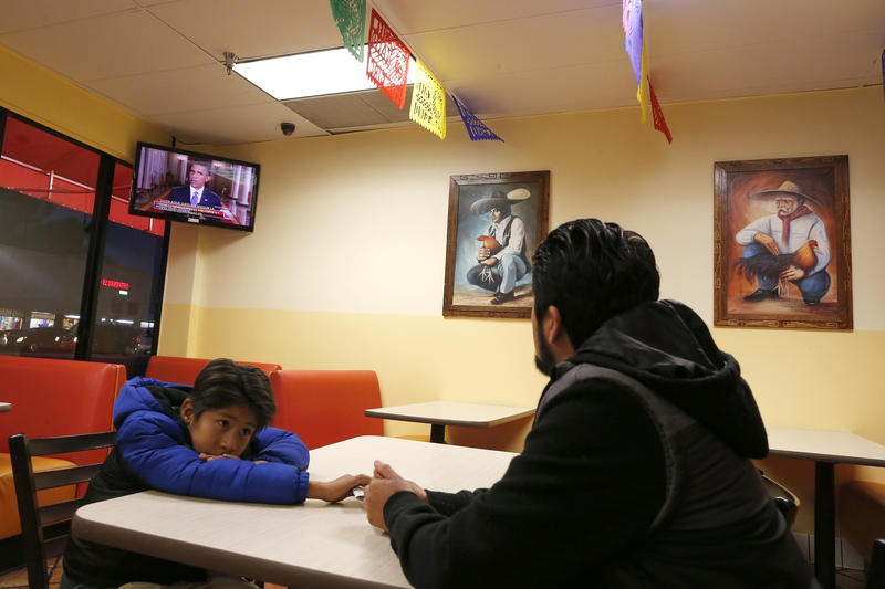 <p>Esteban Cabanas, 30, an undocumented immigrant from Mexico, watches President Barack Obama's White House immigration speech on television with his US-born son Esteban Jr., 7, at a restaurant in Huntington Park, California, on Thursday.</p>