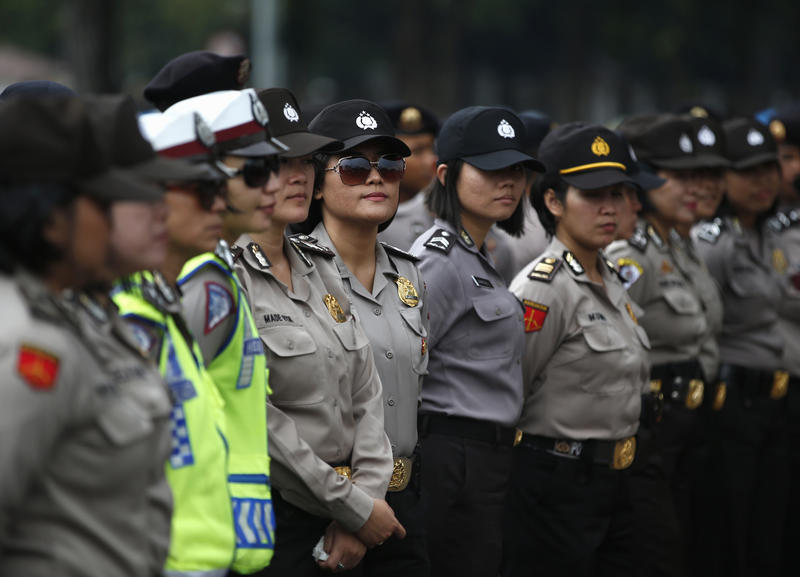 <p>Female Indonesian police officers stand guard outside the presidential palace during a protest against the recent fuel price hike in Jakarta on November 19th, 2014.</p>