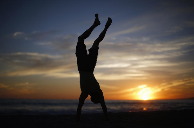 <p>A man does a handstand as the sun sets over the Pacific Ocean on the beach in Santa Monica, California October 3, 2014. </p>