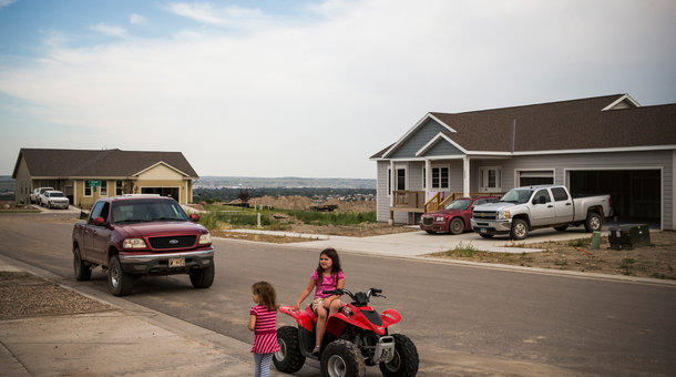 Two girls play on a four-wheeler in a new subdivision in Williston, North Dakota, in 2013. During the last oil boom, researchers estimate the town doubled in size to more than 30,000 people.