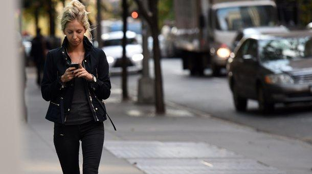 A woman uses her smart phone as she walks on 47th Street November 13, 2014 in New York.