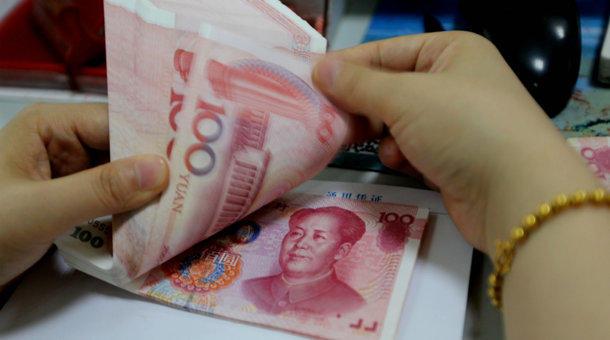 A teller counts yuan banknotes.