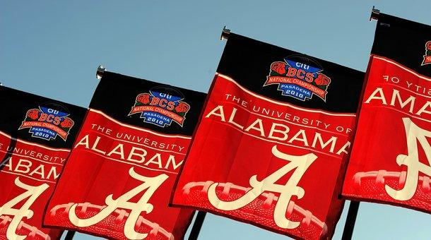 The Alabama Crimson Tide flags wave outside a stadium.