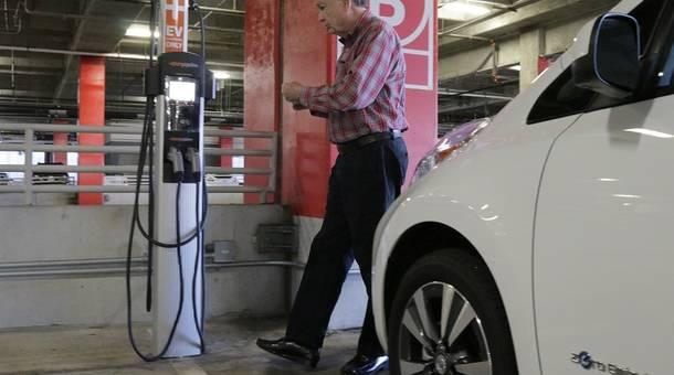 Don Francis, coordinator of Clean Cities Georgia, by his Nissan Leaf at an electric car charging station.