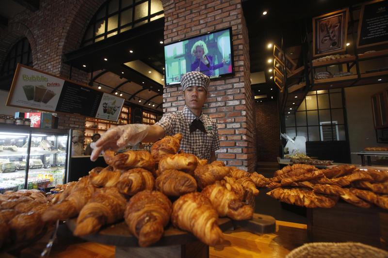<p>A man arranges croissants at a bakery of CBM Corporation in Phnom Penh August 28, 2014.</p>