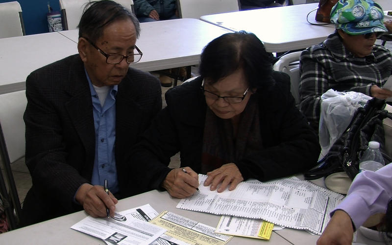 Two churchgoers at the San Diego Living Water Church work on filling in their ballots, May 22, 2016.
