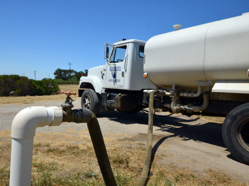 A Crocker Water truck fills underground storage tanks for a homeowner near Paso Robles whose well no longer pumps enough water.