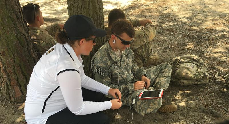 Performance Psychologist Meghan Halbrook of Fort Bragg's Comprehensive Soldier and Family Fitness Center shows a soldier how to use an ear sensor to monitor his stress level as he rests between sessions of machine gun training.
