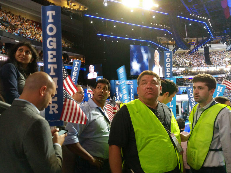 Event staff watch protesters chant during Hillary Clinton's speech accepting her Democratic nomination on July 28, 2016.