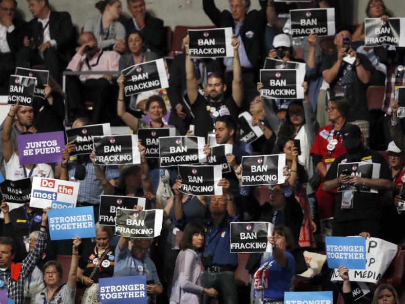 "Signs are held as California Gov. Jerry Brown speaks during the Democratic National Convention on July 27, 2016. During the speech, some California delegates were shouting ""Ban Fracking."""