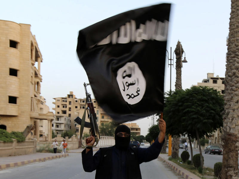 A member loyal to ISIS waves a flag in Raqqa, Syria, in 2014.