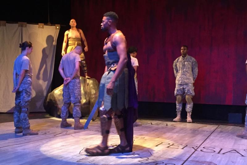 Odysseus (played by Ronin Lee, foreground) ponders what went wrong with Ajax, in the play