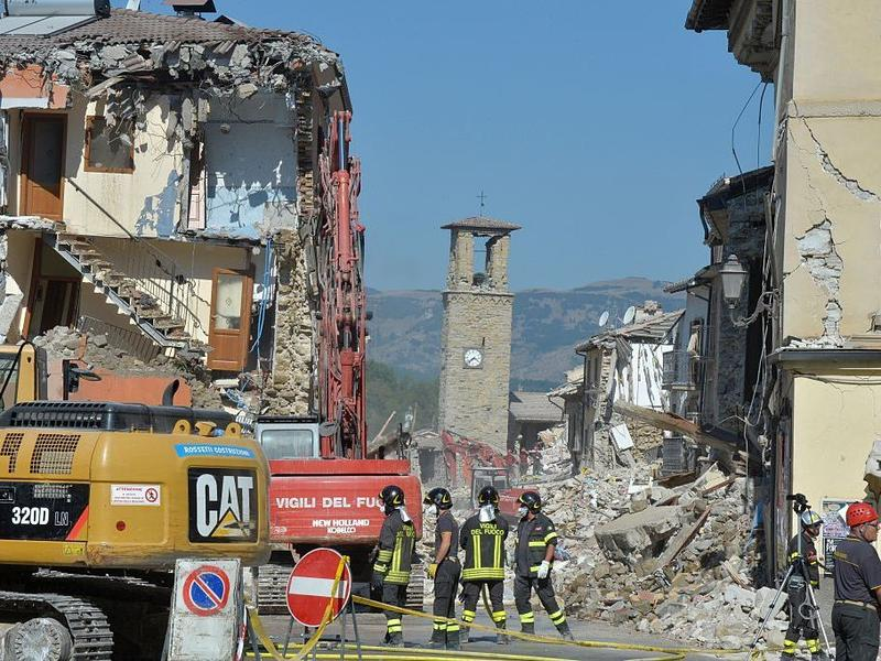 Firefighters gather near the damaged Sant'Agostino church and rubble and debris of destroyed buildings inside a cordoned-off area on Sunday in the central Italian village of Amatrice.