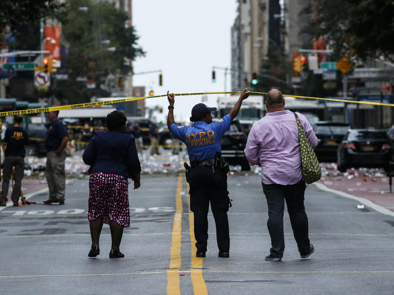 Law enforcement officers keep the scene of an explosion in the Chelsea neighborhood in New York City, on the day after the blast injured dozens.