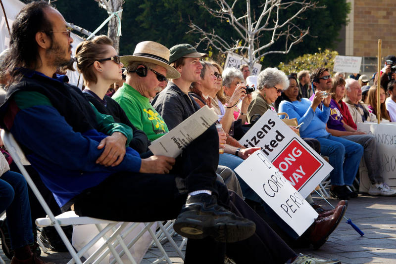 File photo: Several people listen to a speaker express her opposition to the Citizens United ruling at an Occupy Courts protest in Los Angeles.