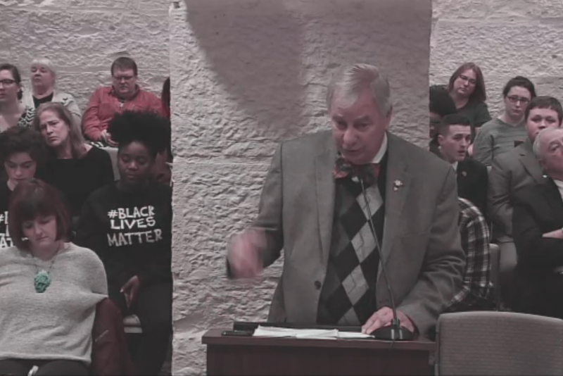 State Sen. James Tomes (R-Wadesville) introduces his bill requiring police to disperse protesters from roadways, while audience members in Black Lives Matter shirts listen. (Indiana Legislature screengrab)
