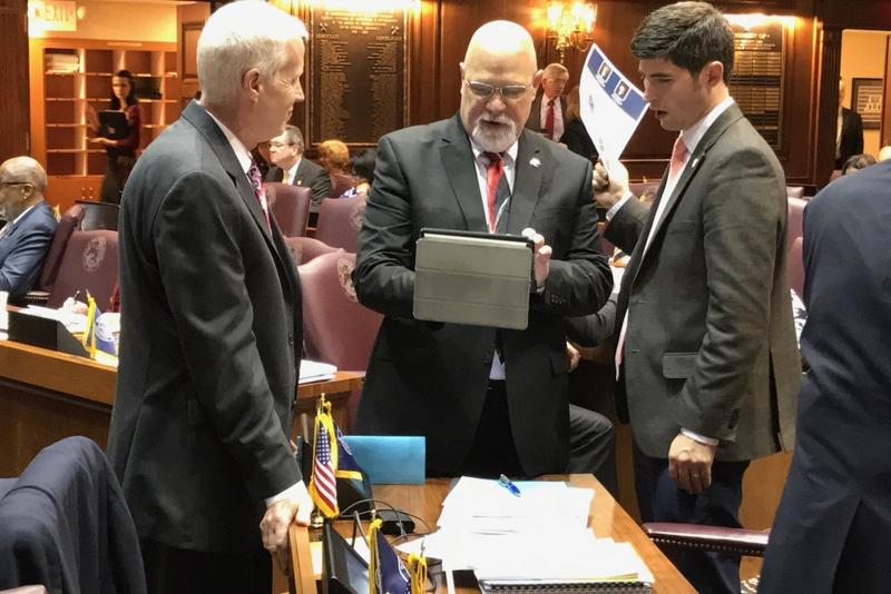 House budget author Rep. Tim Brown (R-Crawfordsville), center, speaks with colleagues on the floor. (Brandon Smith/IPB News)