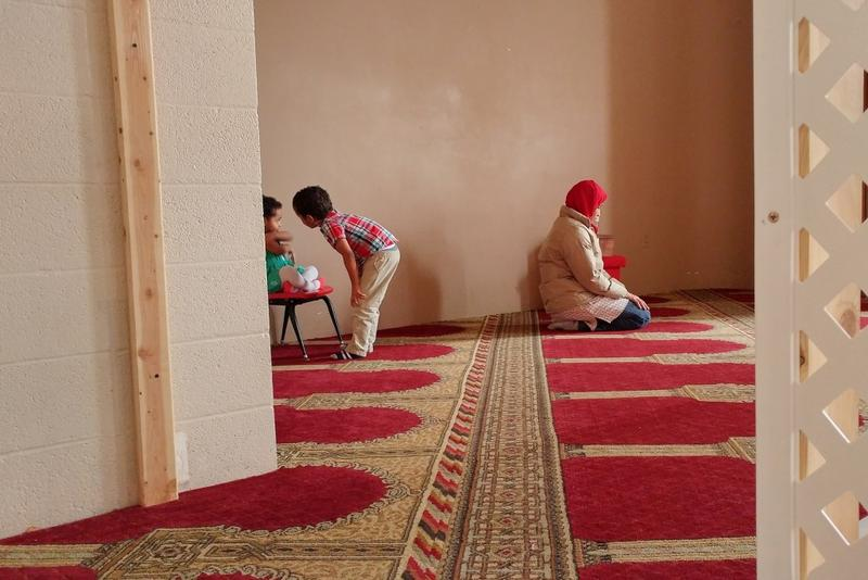 Dalia Mohamed prays before an interview at the Islamic Society of Columbus, Indiana, while her kids, 2-year-old Selma and 5-year-old Mohamed, play nearby. (Annie Ropeik/IPB News)