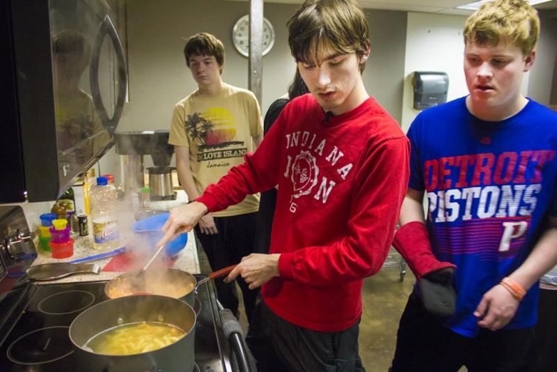 Reagan Roush, center, makes a creamy chicken fajita pasta dish at a weekly cooking skills class at the College Internship Program in Bloomington, Indiana. (Peter Balonon-Rosen/IPB News)