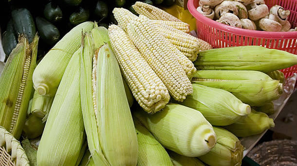 Corn cobs are displayed for sale along with other vegetables in a market in Mexico City.