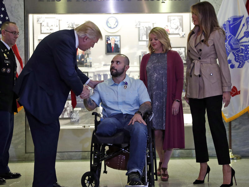 President Donald Trump shakes hands with U.S. Army Sgt. First Class Alvaro Barrientos, after awarding him with a Purple Heart , as first lady Melania Trump, right, stands with Tammy Barrientos second from right, at Walter Reed National Military Medical Ce